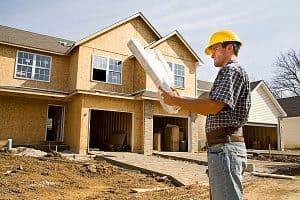 inżynier stojący koło domu
